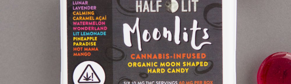 Rectangular box of Half Lit Moonlits Hard Candy with round, multicolored suckers placed around it.