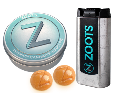 Zoots Rocks Caramel canister next to 2 Rocks with the impression of the letter Z on each. A second round canister is shown for its Zoot Rocks logo