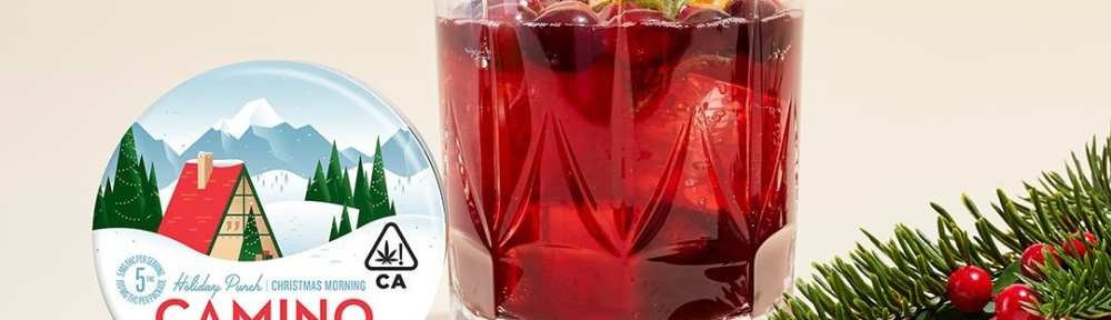 Kiva Camino Holiday Punch Cannabis Infused Gummies next to a glass of red holiday punch